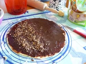 3e etape : la pâte est garnie de chocolat fondu et de noix hachées