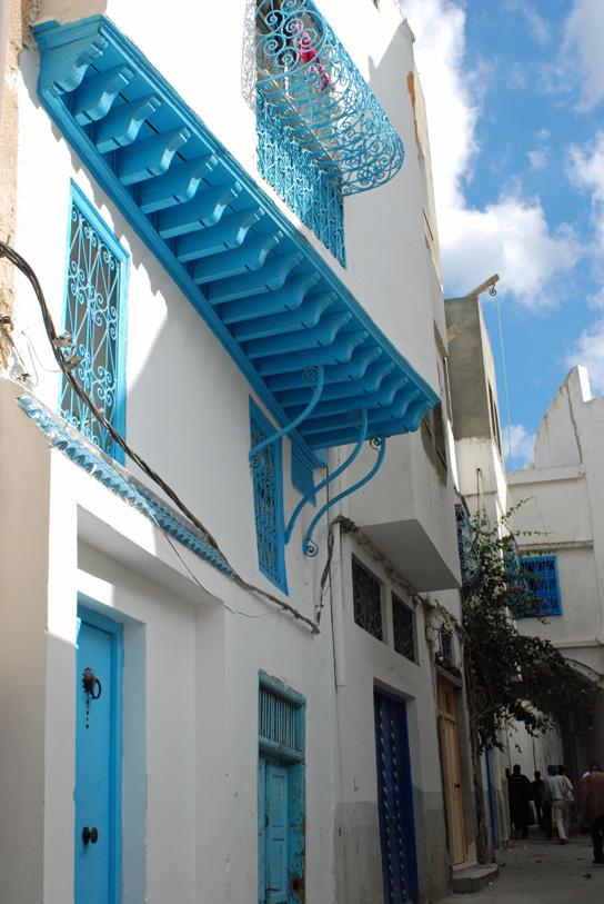Des maisons blanches et bleues au balcon en fer forgé.